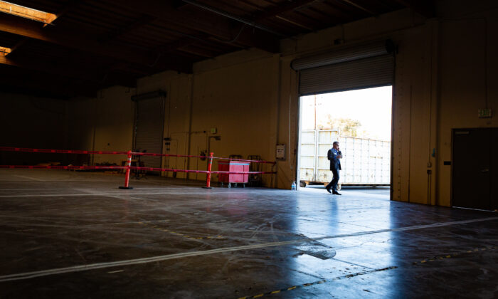 A man stands inside the entrance to an industrial building that will be converted into a homeless shelter in Santa Ana, Calif., on Oct. 30, 2020. (John Fredricks/The Epoch Times)