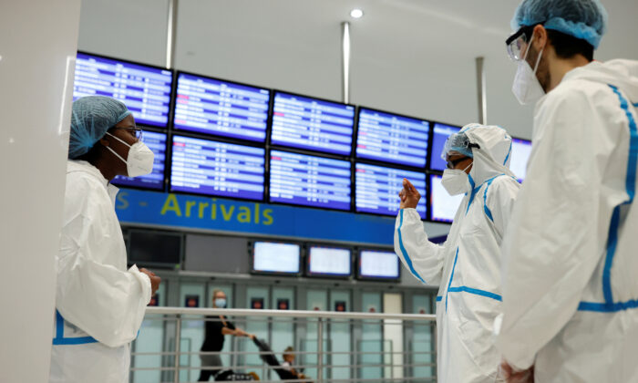 Health workers wearing protective gear wait for passengers to be tested for COVID-19 on arrival at Charles de Gaulle airport in Roissy, near Paris, France, on July 31, 2020. (REUTERS/Christian Hartmann)