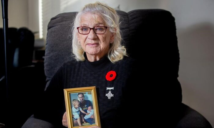Debbie Sullivan holds a photo of her son Christopher Saunders and his two sons while wearing her National Silver Cross at her home in Summerville, New Brunswick, Canada, on Oct. 31, 2020. (James West/The Canadian Press)
