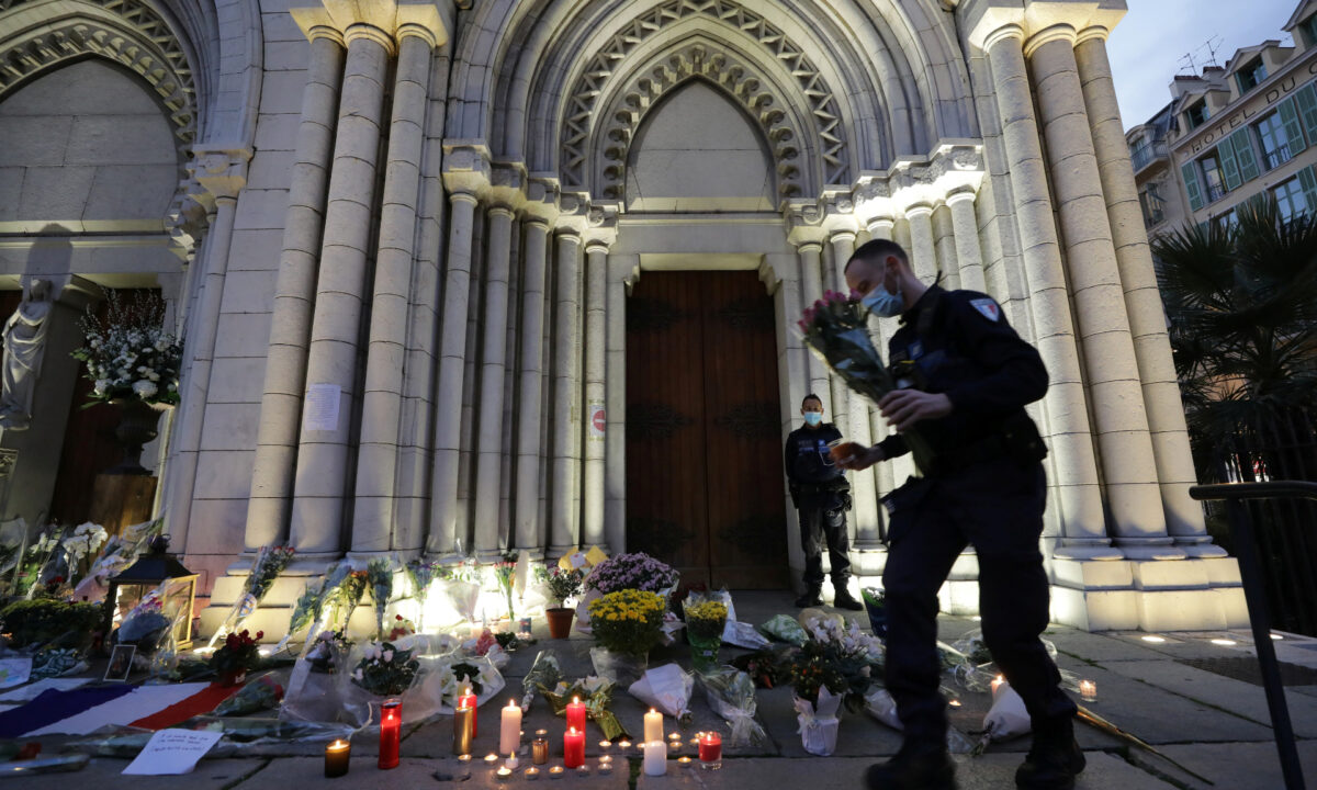 A policeman carries flowers in front of the Notre Dame church