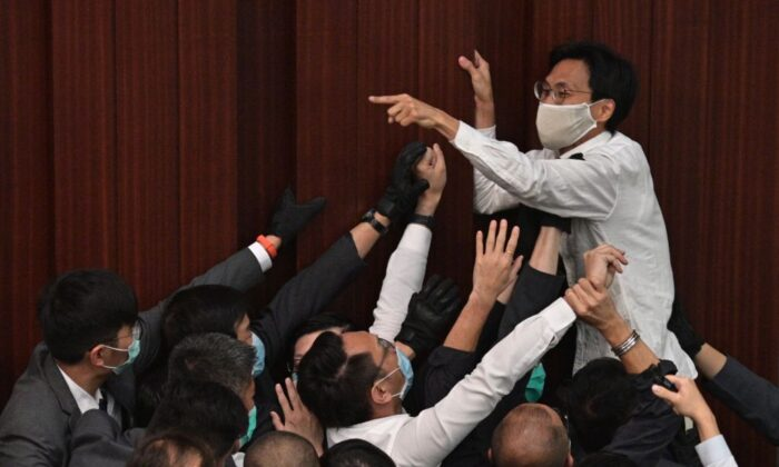 Pro-democracy lawmaker Eddie Chu Hoi-dick (top C) shouts at security trying to restrain at the Legislative Council in Hong Kong on May 8, 2020. (Anthony Wallace/AFP via Getty Images)