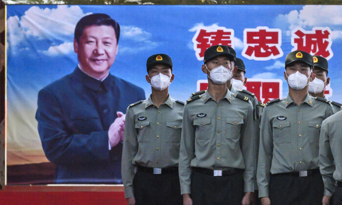 Soldiers of the People's Liberation Army's Honor Guard Battalion wear protective masks as they stand at attention in front of a photo of Chinese Communist Party leader Xi Jinping at their barracks outside the Forbidden City, near Tiananmen Square, in Beijing, on May 20, 2020. (Kevin Frayer/Getty Images)