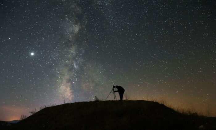 A person takes a photo with a camera on a tripod of the Milky Way (ADEM ALTAN/AFP via Getty Images)