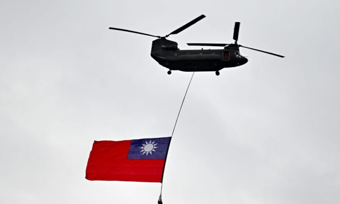 A military helicopter flies with Taiwan's national flag during the National Day in front of the Presidential Office in Taipei on Oct. 10, 2020. (Sam Yeh/AFP via Getty Images)