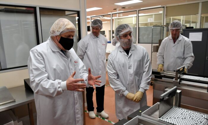 "British Prime Minister Boris Johnson (L) views the ""fill and finish"" stage of the manufacturing process of COVID-19 vaccines during a visit to Wockhardt's pharmaceutical manufacturing facility in Wrexham, Wales, on Nov. 30, 2020. (Paul Ellis/AFP via Getty Images)"