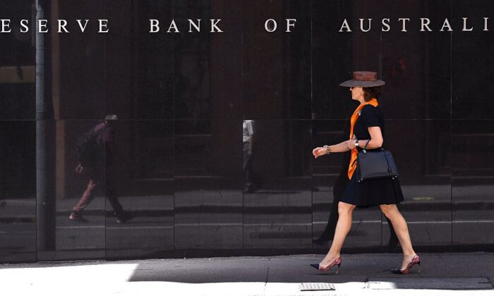 A woman walks past the Reserve Bank of Australia sign in Sydney on October 4, 2016. (WILLIAM WEST/AFP via Getty Images)