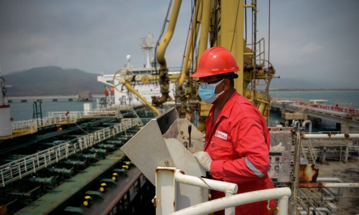 A worker of the Venezuelan state oil company PDVSA looks at the Iranian-flagged oil tanker Fortune as it docks at the El Palito refinery in Puerto Cabello in the northern state of Carabobo, Venezuela, on May 25, 2020. (AFP via Getty Images)