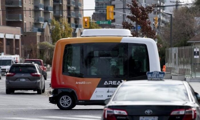 A low-speed autonomous shuttle rides past a taxi during a demonstration on roads around government buildings in Ottawa, on Nov. 2, 2020. (The Canadian Press/Adrian Wyld)