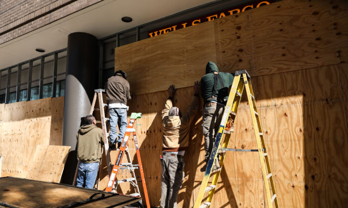 Workers board up store windows in preparation for Election Day, in downtown Washington near the White House, on Nov. 2, 2020. (Charlotte Cuthbertson/The Epoch Times)