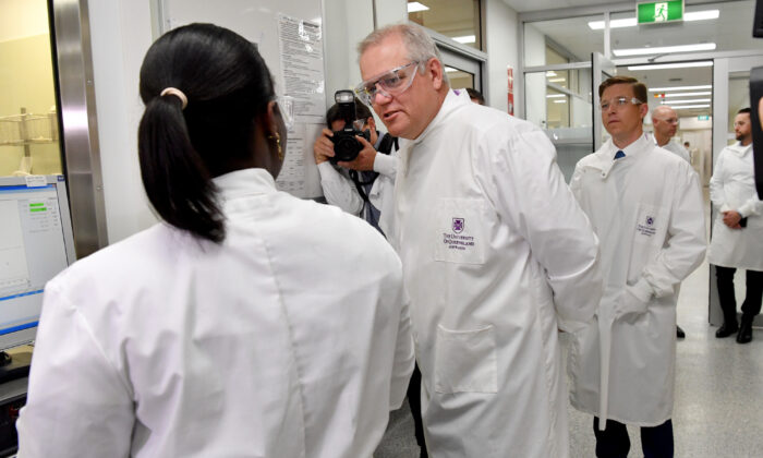 Prime Minister Scott Morrison (centre) is seen during a tour of the University of Queensland Vaccine Lab in Brisbane, Monday, Oct. 12, 2020. (AAP Image/Darren England)