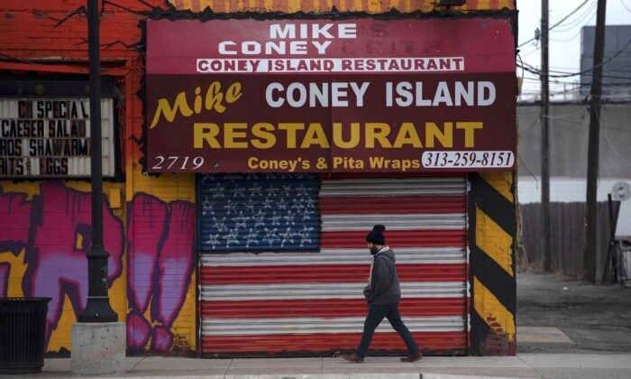 A man passes a closed restaurant in Detroit, Mich., on March 24, 2020. (Seth Herald/AFP via Getty Images)