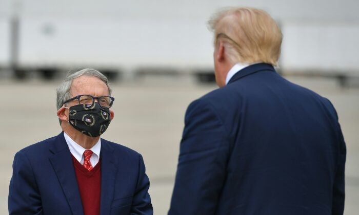 President Donald Trump speaks with Ohio Gov. Mike DeWine upon arrival at Rickenbacker International Airport in Columbus, Ohio on Oct. 24, 2020. (Mandel Ngan/AFP via Getty Images)