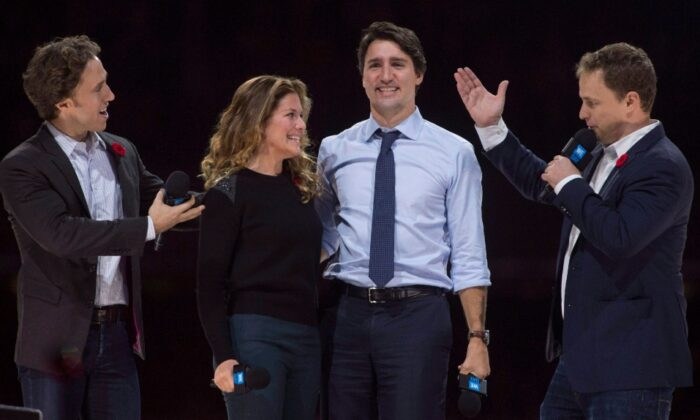Co-founders Craig (L) and Marc Kielburger introduce Prime Minister Justin Trudeau and his wife Sophie Gregoire-Trudeau as they appear at the WE Day celebrations in Ottawa on November 10, 2015. (The Canadian Press /Adrian Wyld)