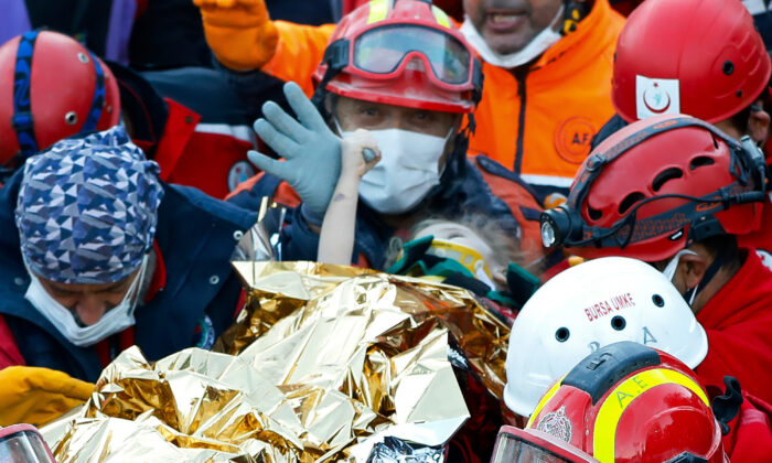 Members of various rescue services carry 3-year-old girl Elif Perincek, after she was rescued from the rubble of a building some 65 hours after a magnitude 6.6 earthquake in Izmir, Turkey, on Nov. 2, 2020. (Istanbul Fire Authority via AP)