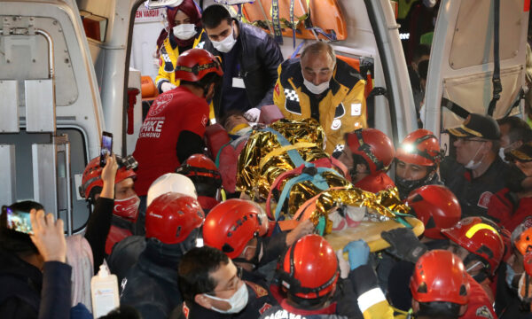 Rescue workers, who were trying to reach survivors in the rubble of a collapsed building, carry to an ambulance 14-year-old Idil Sirin