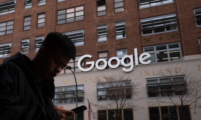 A man using a mobile phone walks past Google offices in New York on Dec. 17, 2018. (Mark Lennihan/AP Photo)
