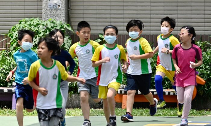 Students run during a sports class at Dajia Elementary School in Taipei on April 29, 2020. (Sam Yeh/AFP via Getty Images)