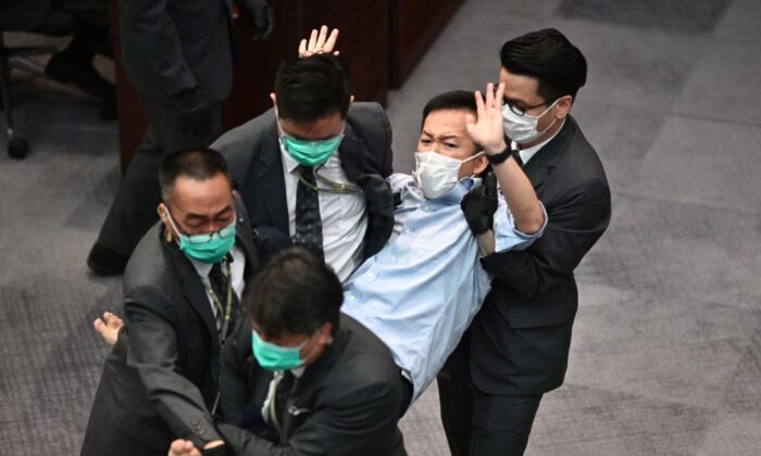 Pro-democracy lawmaker Raymond Chan (C) is carried away by security following scuffles at the Legislative Council (LegCo) in Hong Kong on May 8, 2020. (Anthony Wallace/AFP via Getty Images)