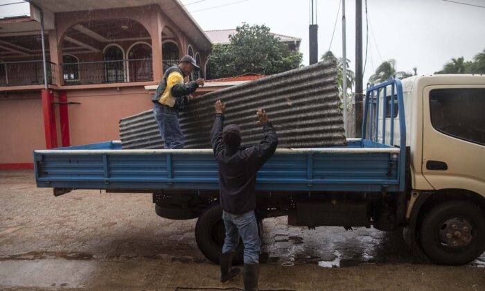 Workers carry zinc sheets to protect windows before the arrival of Hurricane Eta, in Bilwi, Puerto Cabezas, Nicaragua, on Nov. 2, 2020. (Inti Ocon/AFP via Getty Images)