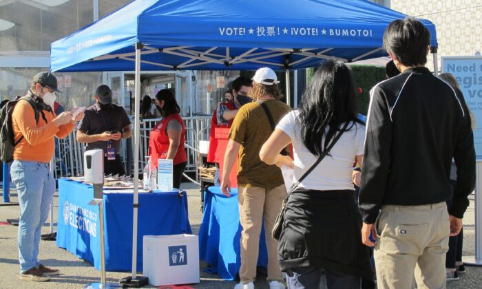 People drop off their ballots at a booth near the Bill Graham Civic Auditorium in San Francisco on Oct. 31, 2020. (Ilene Eng/The Epoch Times)