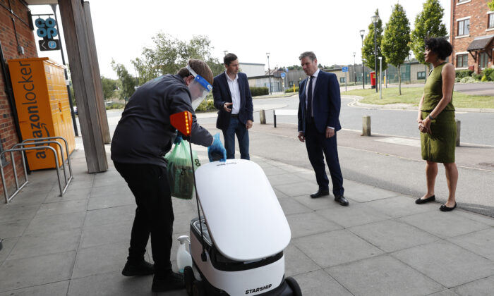 The Labor Leader Keir Starmer, the Shadow Minister for Science, Research and Digital Chi Onwurah, and  Starship Technologies' VP of Marketing Henry Harris-Burlan watch a Co-op supermarket worker load groceries into a Starship delivery robot on July 23, 2020 in Milton Keynes, England. (Darren Staples/Getty Images)