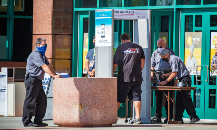 Security personnel watch a man pass through a metal detector as he prepares to enter a temporary voting center set up inside the Honda Center in Anaheim, Calif., on Nov. 2, 2020. (John Fredricks/The Epoch Times)