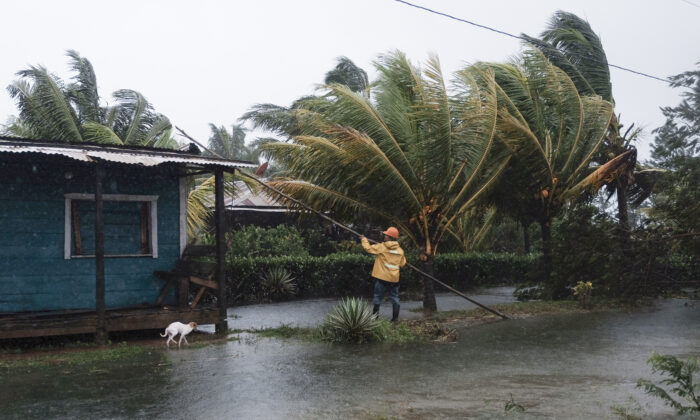 A man fixes the roof of a home surrounded by floodwaters brought on by Hurricane Eta in Wawa, Nicaragua, on Nov. 3, 2020. (Carlos Herrera/AP Photo)