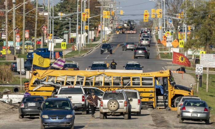 Six Nations protesters gather by a destroyed school bus blocking Argyle Street in Caledonia, Ont., on Oct. 28, 2020. (The Canadian Press/Frank Gunn)