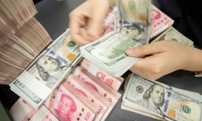A Chinese bank employee counts 100-yuan notes and US dollar bills at a bank counter in Nantong in eastern China's Jiangsu Province on Aug. 6, 2019. (STR/AFP via Getty Images)