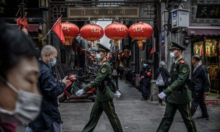 Chinese police patrol as tourists walk in a busy shopping area during the final day of the Golden Week holiday in Beijing on Oct. 8, 2020. (Kevin Frayer/Getty Images)