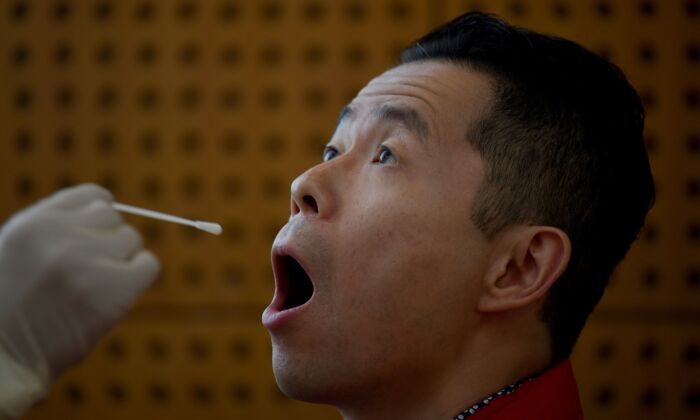 A journalist undergoes a swab test for COVID-19, part of health requirements for media workers covering a government event in Beijing on Oct. 22, 2020. (NOEL CELIS/AFP via Getty Images)
