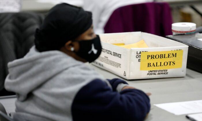 An election worker waits to receive absentee ballots to check they are properly filled out for the general election at TCF Center in Detroit, Michigan, on Nov. 3, 2020. (JEFF KOWALSKY/AFP via Getty Images)