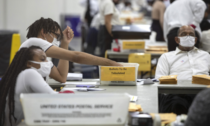 A worker with the Detroit Department of Elections sorts through absentee ballots at the Central Counting Board in the TCF Center in Detroit on Nov. 4, 2020. (Elaine Cromie/Getty Images)