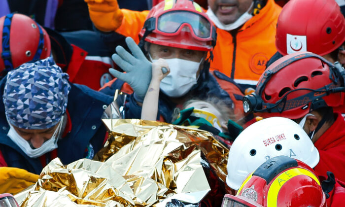 Members of various rescue services carry 3-year-old girl Elif Perincek after she was rescued from the rubble of a building some 65 hours after a magnitude 6.6 earthquake in Izmir, Turkey, Nov. 2, 2020. (Istanbul Fire Authority via AP)