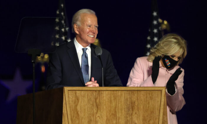 Democratic presidential nominee Joe Biden speaks at a drive-in election night event, with his wife Jill Biden clapping, at the Chase Center in Wilmington, Del., early Nov. 4, 2020. (Win McNamee/Getty Images)