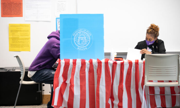 Sitting next to a poll worker, a Fulton County voter casts a ballot at the Metropolitan Library in Atlanta, Ga., on Nov. 3, 2020. (Jessica McGowan/Getty Images)