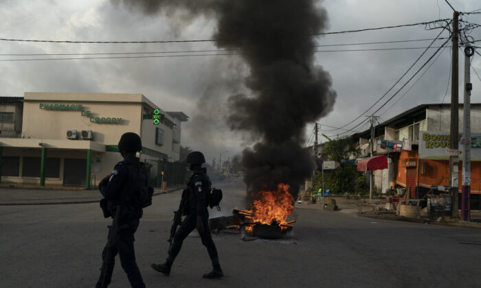 Policemen walk past a burning barricade during a protest after the security forces blocked the access to the house of the former president Henri Konan Bedie, in Abidjan, Ivory Coast on Nov. 3, 2020. (Leo Correa/AP Photo)
