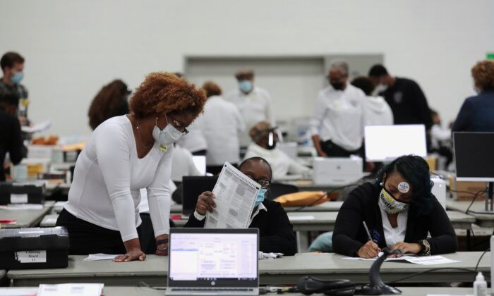 Poll workers tabulate absentee ballots at the TCF Center during Election Day in Detroit, Mich., Nov. 3, 2020. (Rebecca Cook/Reuters)