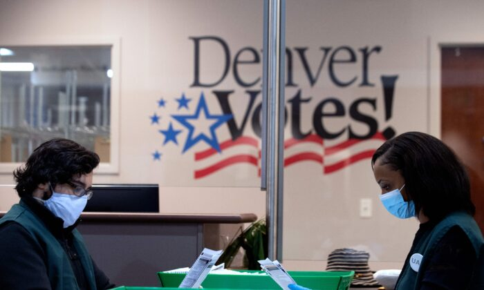 Poll workers review voter ballots at the Denver Elections Division headquarters in Denver, Colo., on Nov. 3, 2020. (Jason Connolly/AFP via Getty Images)