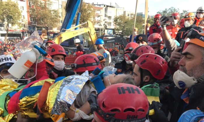 In this photo provided by Turkey's IHH humanitarian aid group, Ayda Gezgin is carried by members of rescue services and medics after she was taken out of the rubble of her collapsed building, in Izmir, Turkey, on Nov. 3, 2020. (IHH via AP)