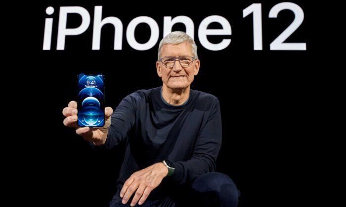 Apple CEO Tim Cook poses with the all-new iPhone 12 Pro at Apple Park in Cupertino, Calif., on Oct. 13, 2020. (Brooks Kraft/Apple Inc./Handout via Reuters)