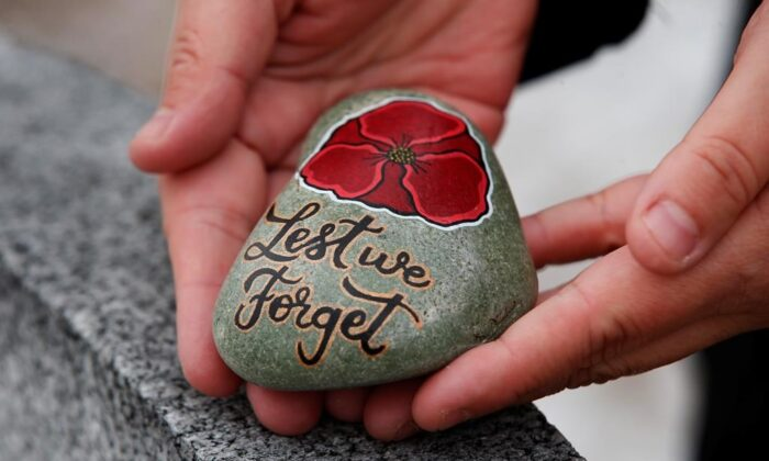 Julie Mungall places her painted stones at the Brookside veterans cemetery in Winnipeg, on Oct. 24, 2020. (The Canadian Press/John Woods)