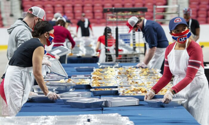 Volunteers prepare meals for food banks on the floor of the Bell Centre in Montreal on May 5, 2020. (The Canadian Press/Ryan Remiorz)