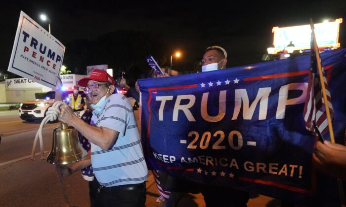 Rafael Fagundo rings a bell as he and other supporters of President Donald Trump chant and wave flags outside the Versailles Cuban restaurant during a celebration on election night in the Little Havana neighborhood of Miami on Nov. 3, 2020. (Wilfredo Lee/AP Photo)