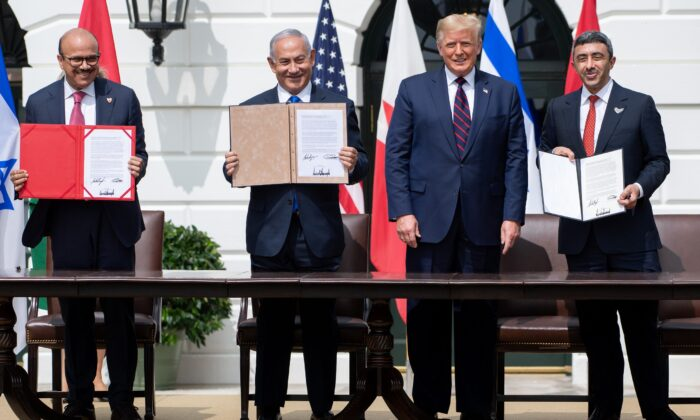 (L-R) Bahrain Foreign Minister Abdullatif al-Zayani, Israeli Prime Minister Benjamin Netanyahu, U.S. President Donald Trump, and UAE Foreign Minister Abdullah bin Zayed Al-Nahyan hold up documents after participating in the signing of the Abraham Accords where the countries of Bahrain and the United Arab Emirates recognize Israel, at the White House in Washington on Sept. 15, 2020. (Saul Loeb/AFP via Getty Images)