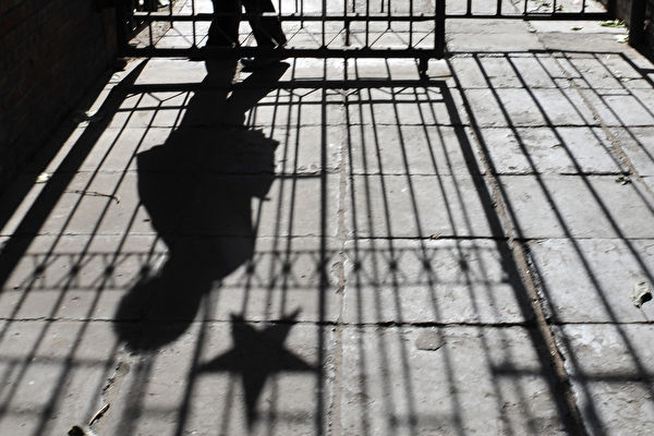 A woman walking between a metal gate adorned with a communist star insignia at an old Beijing residential compound casts a shadow against the morning sun on Nov. 15, 2008. (FREDERIC J. BROWN/AFP/Getty Images)