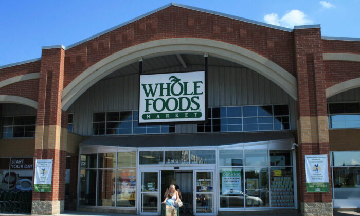 A customer leaves a Whole Foods Market store in Oakville, Ont., Canada on Aug. 22, 2012. (Richard Buchan/The Canadian Press)