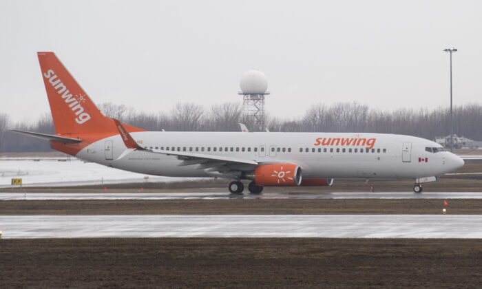 A Sunwing Airlines jet prepares to take off at Montreal's Trudeau International Airport on March 20, 2020, as COVID-19 cases rise in Canada and around the world. (The Canadian Press/Graham Hughes)