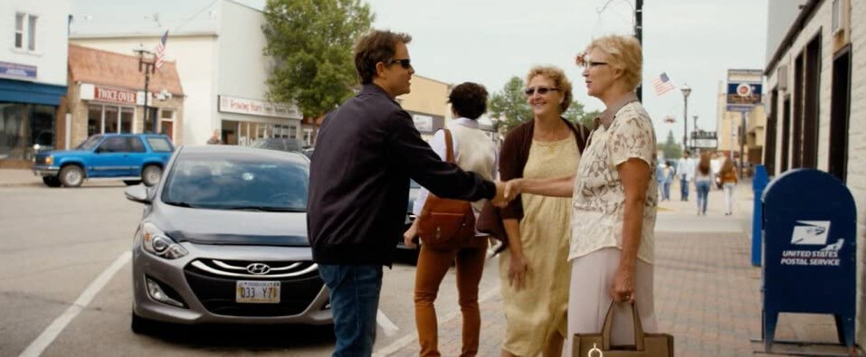 """man in sunglasses shakes hands with woman in """"Heaven is for Real"""""""