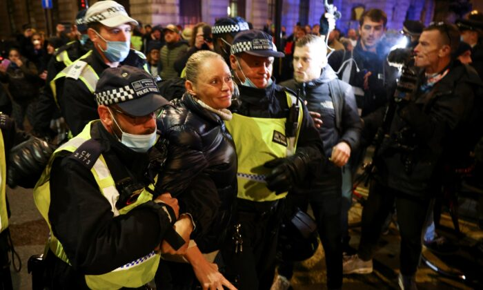 A woman is detained by police officers as protestors from the Million Mask March and anti lockdown protesters demonstrate, amid the CCP virus outbreak in London, on Nov. 5, 2020. (Henry Nicholls/Reuters)